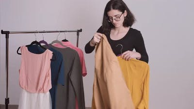 Girl Chooses Clothes From the Rack Picking Up Clothes for a Meeting Puts on a Jacket She Liked