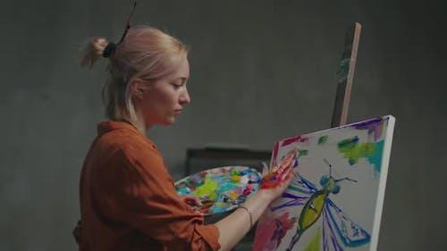 Inspired Artist Creating Fingerpaint on Canvas in Art Studio