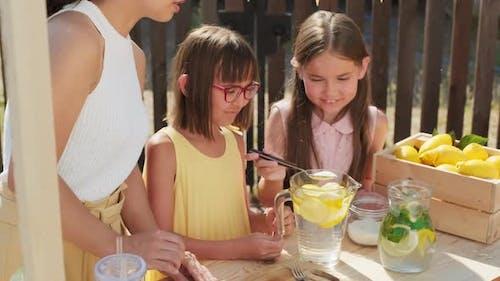 10-Year-Old Girls Making Lemonade Outdoors