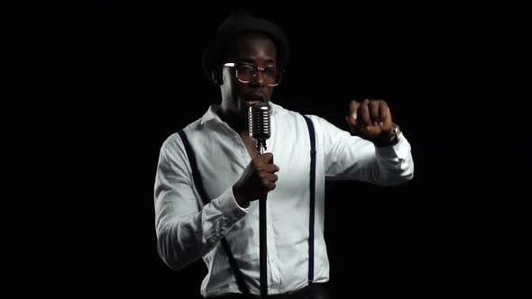 Thumbnail for Singer Sings Into a Microphone Spinning Jumping and Dancing Around Him. Black Background. Slow