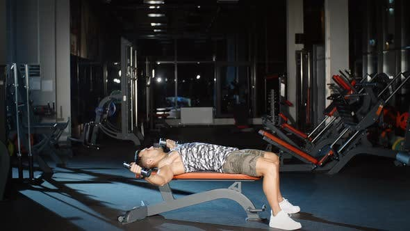Thumbnail for Attractive Athlete Working Out and Training his Arms and Shoulders With Dumbbell on Bench in Gym
