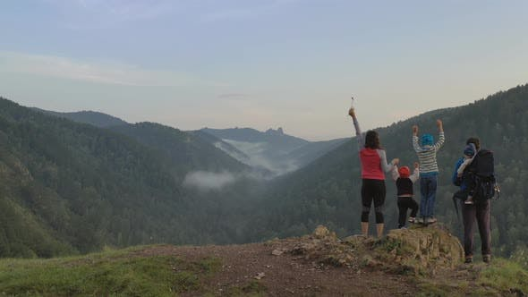 A Happy Family with Three Children Cheerfully Raise Their Hands Standing on the Top of the Mountain