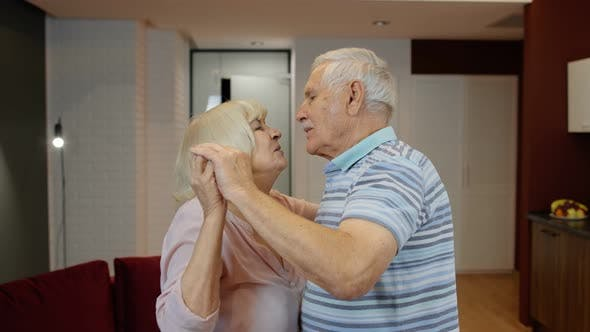 Thumbnail for Happy Carefree Elderly Senior Grandparents in Love Dancing Waltz in Modern Living Room at Home