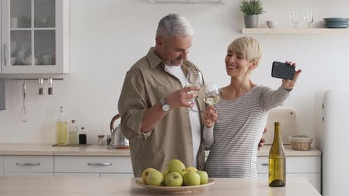 MiddleAged Couple Making Selfie Clinking Glasses With Wine In Kitchen