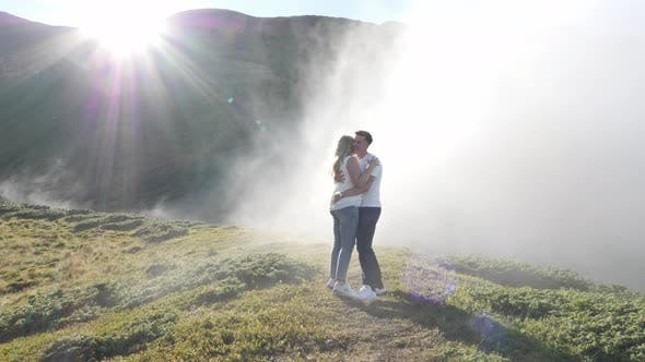 Thumbnail for Couple hugging on a hill