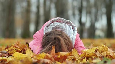 Teenage Girl Crying in the Autumn Foliage in the Park