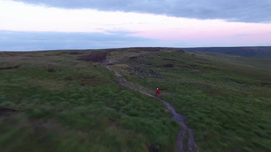 Thumbnail for Aerial shot of a mountain biker on a singletrack trail.