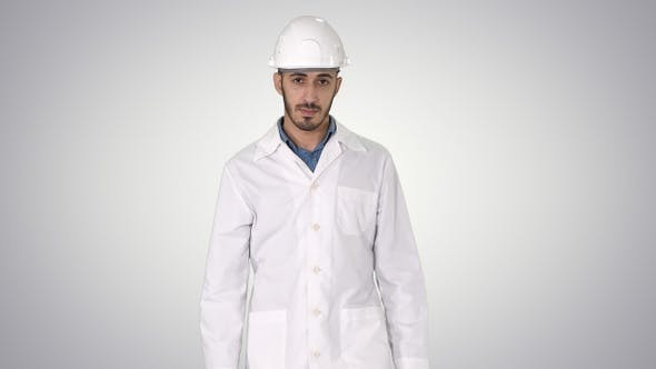 Thumbnail for Arab engineer in helmet and white robe walking forward