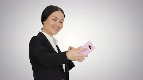 Smiling Businesswoman Taking Selfie on Her Phone on Gradient Background