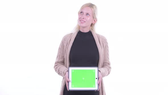 Cover Image for Happy Young Blonde Pregnant Woman Thinking While Showing Digital Tablet