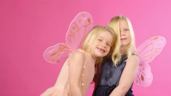Cover Image for Dressed-Up Twin Sisters Posing and Smiling