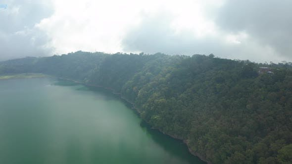 Thumbnail for Drone Over Green Forest And Lake Under Cloudy Sky