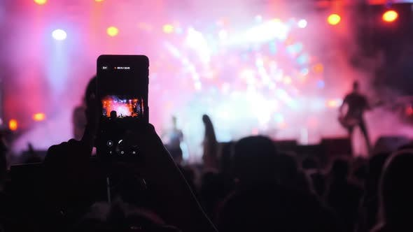 Silhouette of Woman Hands Making Video with Smartphone at Live Rock Concert. Slow Motion