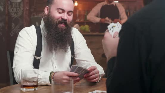 Thumbnail for Man with Long Beard Smiling and Playing Cards with a Friend