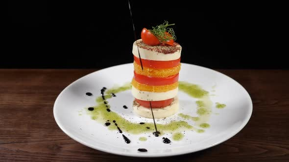Thumbnail for Fine Cuisine in Restaurant. Pouring Vinegar Sauce on Mozzarella Salad in Slow Motion. Food Footage
