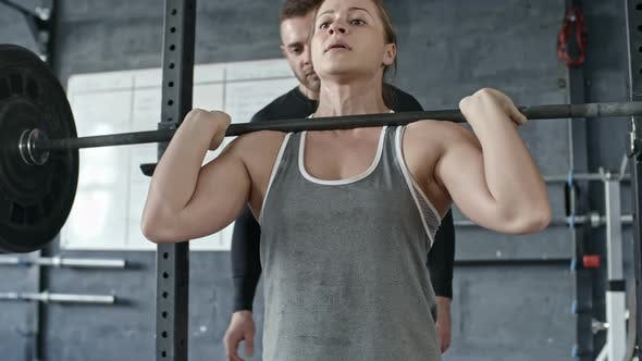 Cover Image for Coach Assisting Muscular Woman Lifting Heavy Barbell