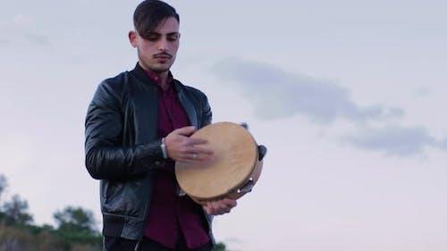 Man with tambourine at sunset