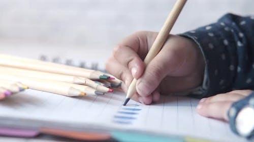 Gros plan d'un dessin à la main d'un enfant avec un crayon de couleur sur une page