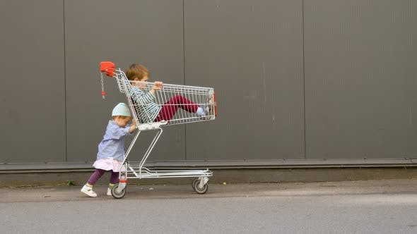 Cover Image for Little Girl Pushing Shopping Cart with Brother Sitting in It. Children Entertainments While Waiting