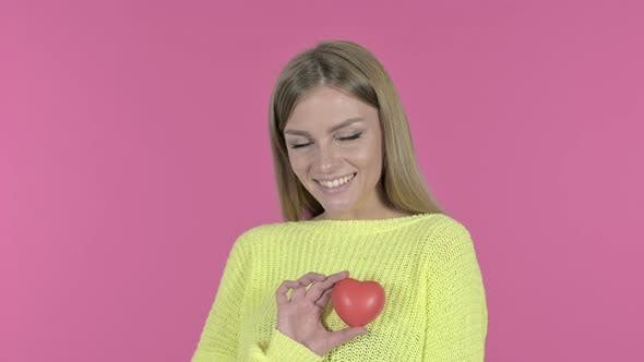 Thumbnail for Happy Young Girl Holding Red Heart, Pink Background