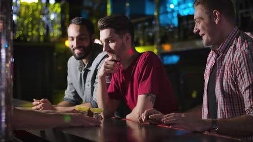 Three Young Men Standing at Bar Counter and Talking with Bartender, Barkeeper Giving Short Drinks