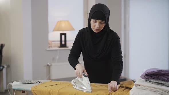 Thumbnail for Porträt von müde muslimische Frau in schwarz traditionelle Kleidung tun Hausarbeit. Junge schöne Dame in