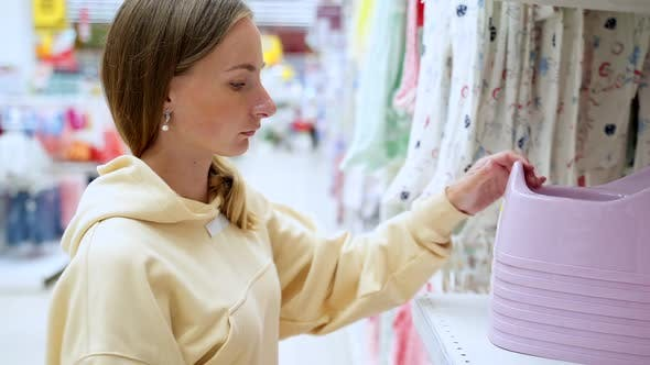 Thumbnail for Mother Buys Clothes for Her Baby in a Children's Clothing Store. The Girl Chooses Clothes