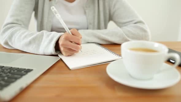 Thumbnail for Woman writing on notebook on her desk