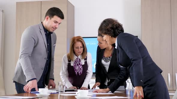 Thumbnail for Business Team in Conference Room Looking at Papers with Charts