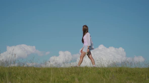 Girl Walks on the Green Grass with Blue Sky in the Background