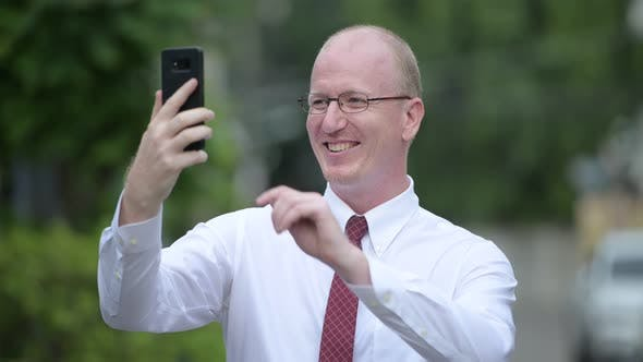 Thumbnail for Happy Mature Bald Businessman Smiling and Taking Selfie Outdoors