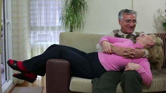 Thumbnail for Senior Couple Talking While Sitting On Sofa