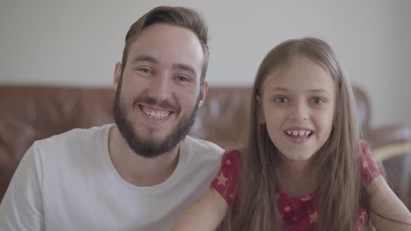 Thumbnail for The Handsome Bearded Man and Cute Positive Girl Looking in the Camera Smiling. The Child Leans Her