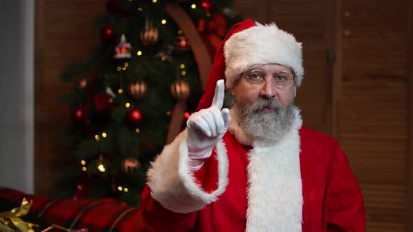 Thumbnail for Porträt eines Weihnachtsmanns, der in die Kamera schaut und allen an den Feiertagen gratuliert