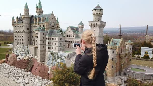 Thumbnail for Woman Makes Photo Walking on Foot Near a Miniature Model of the Old Castle Neuschwanstein, Germany