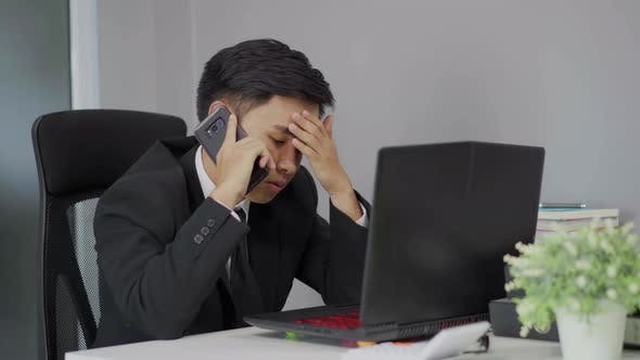 depressed man in suit is talking on smartphone