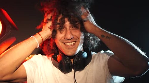 MAle Dj with Afro Hairstyle Play Music and Dance in a Club