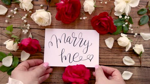 Hands with MARRY ME card