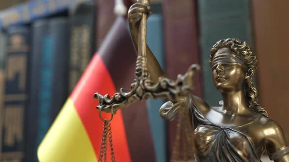 Thumbnail for Statue of Lady Justice with Bookshelf with Books and Germany Flag Background