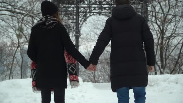 Thumbnail for Young Man and Woman Walking in Winter Park Covered with Snow Holding Hands. Winter Leisure