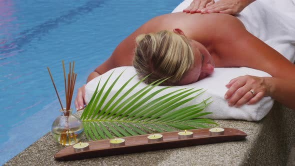 Woman laying by pool getting back massage. Shot on RED EPIC for high quality 4K, UHD, Ultra HD resol