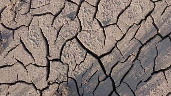 Thumbnail for Looking down at the cracked surface of a dry river