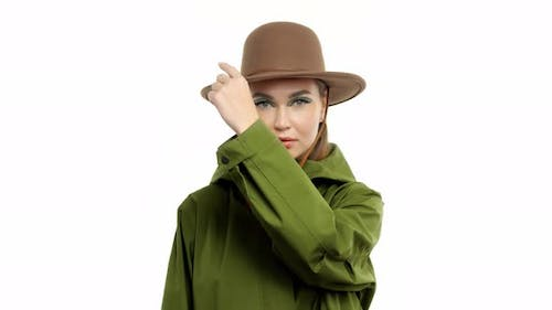 Woman in a Autumn Look in Studio in Green Parka and Hat Turns and Poses To the Camera