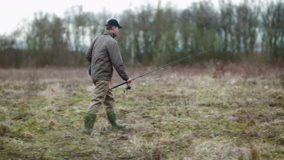 Thumbnail for Man Holding Fishing Rod Walking Amidst Bare Trees