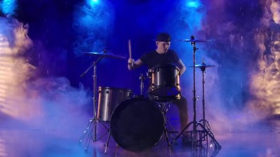 Young Man Enthusiastically Plays the Drum Kit with Drumsticks