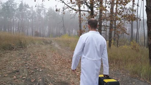 In the Forest, an Ecologist Walks with a Tool Box. Environmental Pollution Studies