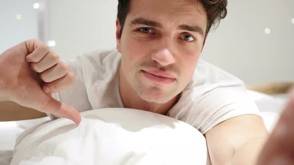 Thumbnail for Thumbs Down by Man Lying in Bed on Stomach, Disliking