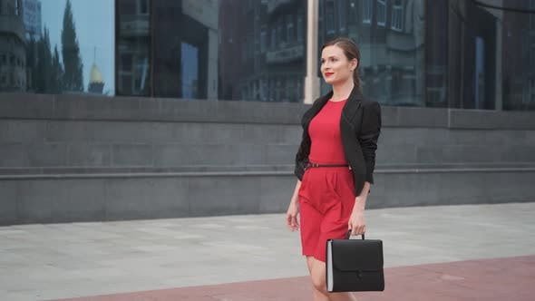 Thumbnail for Self-confident Business Woman in a Red Dress Walking Alongside a Business Center, Young Woman