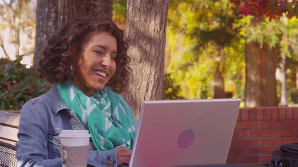 College student on campus in fall using laptop computer