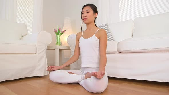 Thumbnail for Chinese woman meditating in living room